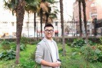 Homme d'affaires chinois debout à l'extérieur tenant une tasse de café, Espagne — Photo de stock