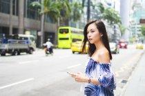 Jolie asiatique fille dans l 'rue avec smartphone — Photo de stock