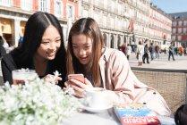 Donne asiatiche in un caffè utilizzando smartphone a Madrid, Spagna — Foto stock