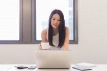 Jeune femme travaillant avec son ordinateur portable dans le bureau moderne — Photo de stock