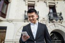 Homem de negócios chinês mensagens de texto no telefone na rua em Madrid, Espanha — Fotografia de Stock