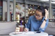 Giovane donna annotando alcune informazioni in un caffè . — Foto stock