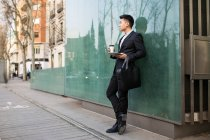 Chinese businessman standing outdoors holding a cup of coffee and a tablet computer, Spain — Stock Photo