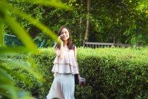 Schön asiatische Mädchen mit Telefon in die Straße — Stockfoto