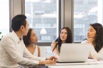 Jeunes collègues asiatiques travaillant dans un bureau moderne — Photo de stock