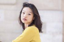 Retrato de uma jovem mulher chinesa sexy e exótica em uma camisa amarela olhando para cima com os olhos fechados — Fotografia de Stock