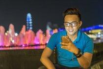 Jovem jogando com seu smartphone na cidade — Fotografia de Stock