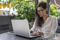 Joven hermosa mujer asiática usando laptop - foto de stock