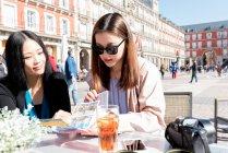 Donne asiatiche sedute in un caffè e guardando la mappa a Madrid, Spagna — Foto stock