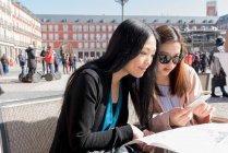Donne asiatiche in un bar utilizzando la mappa in Madrid, Spagna — Foto stock