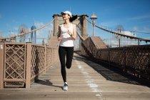 Piuttosto asiatico corridore ragazza formazione all'aperto lavorando fuori a Brooklyn ponte con Manhattan, New York City in background . — Foto stock