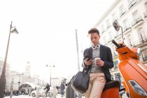 Un joven chino casual con un teléfono inteligente. auriculares y una taza de café en Puerta del Sol, Madrid, España - foto de stock