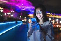 Молодий леді, використовуючи свій мобільний телефон на вулиці, ніч світлому фоні — стокове фото