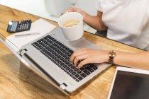 Imagen recortada de mujer joven que trabaja con el ordenador portátil - foto de stock