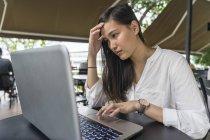 Joven hermosa mujer asiática usando laptop — Stock Photo