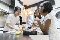 Щаслива родина азіатських святкування Харі Райян вдома і приготування їжі на кухні — стокове фото