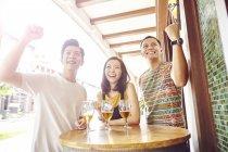 Giovani amici asiatici tifo insieme nel bar — Foto stock
