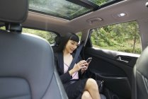 Businesswoman using her mobile in the backseat of a car — Stock Photo
