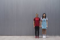 Young asian college students posing against wall — Stock Photo