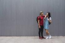 Estudiantes universitarios jóvenes de Asia que se enfrentan a un muro gris - foto de stock