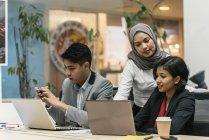 Jovens empresários multiculturais que trabalham com dispositivos digitais em escritórios modernos — Fotografia de Stock