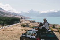Back view of young man sitting on top of car in Milford Sound, New Zealand — Stock Photo