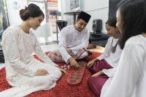 Heureux asiatique famille célébrant hari raya à la maison et jouer jeu traditionnel — Photo de stock