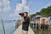 Молодой фотограф фотографирует в рыбацкой деревне Пан Ао Яй — стоковое фото