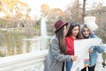 Mulheres que olham para um mapa de Madrid junto ao lago Retiro Park Madrid, Espanha — Fotografia de Stock
