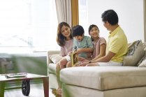 Family bonding over a book reading session at home — Stock Photo