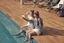 Attractive young asian women taking selfie near pool — Stock Photo