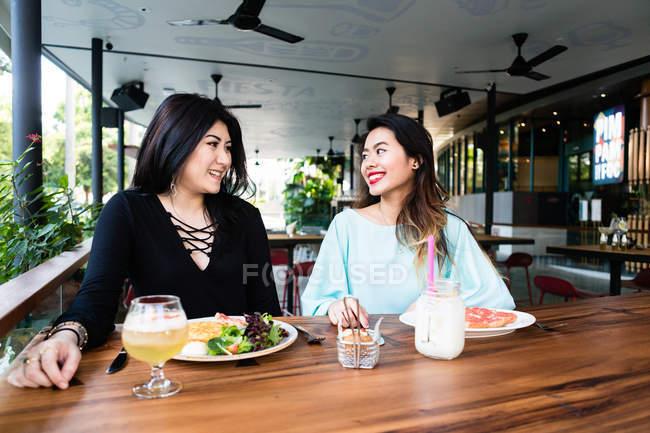 Jeunes femmes partageant un repas dans un café ensemble — Photo de stock