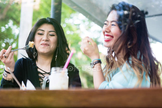 Young women having a meal at a cafe together. — Stock Photo