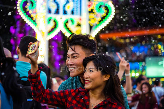 Happy asian couple spending time together in amusement park at christmas and taking selfie — Stock Photo