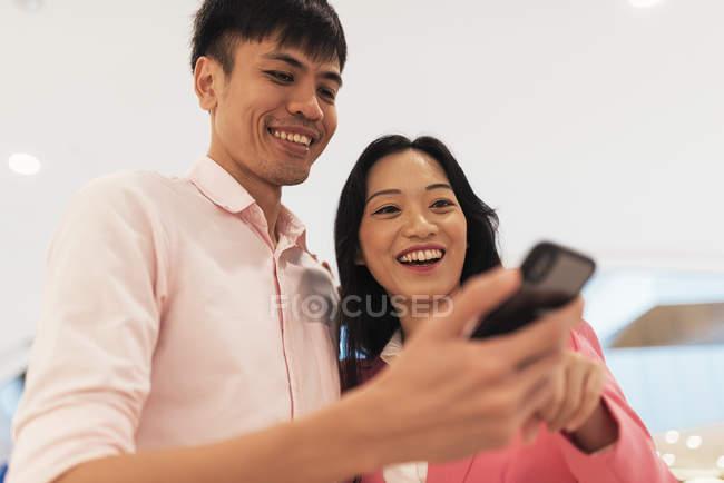Привлекательные молодые Азиатская пара обмена смартфон вместе — стоковое фото