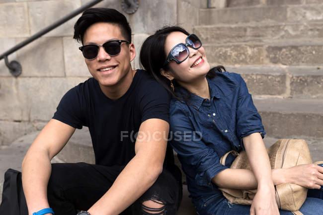 Junge Chinesen mit Sonnenbrille sitzen zusammen auf Stufen — Stockfoto