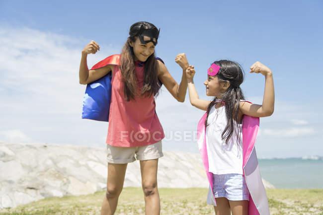 Madre e figlia che flettono i muscoli in spiaggia — Foto stock
