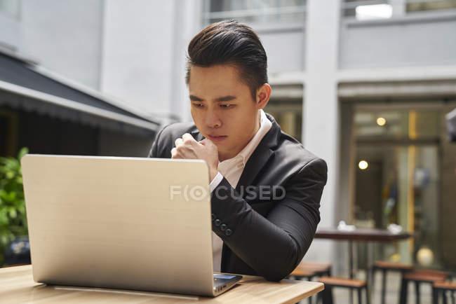 Uomo giovane asiatico business di successo utilizzando il computer portatile — Foto stock