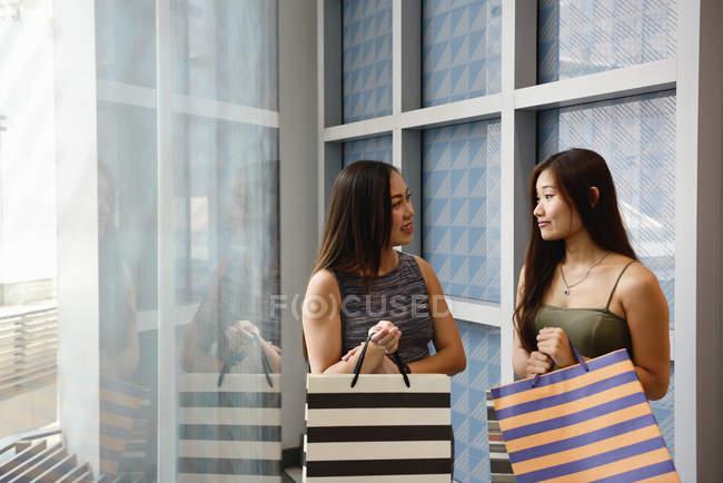 Dos mujeres asiáticas con bolsas de compras en el centro comercial - foto de stock
