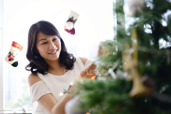 Famiglia asiatica felice alle vacanze di Natale, donna che decora l'albero di abete — Foto stock