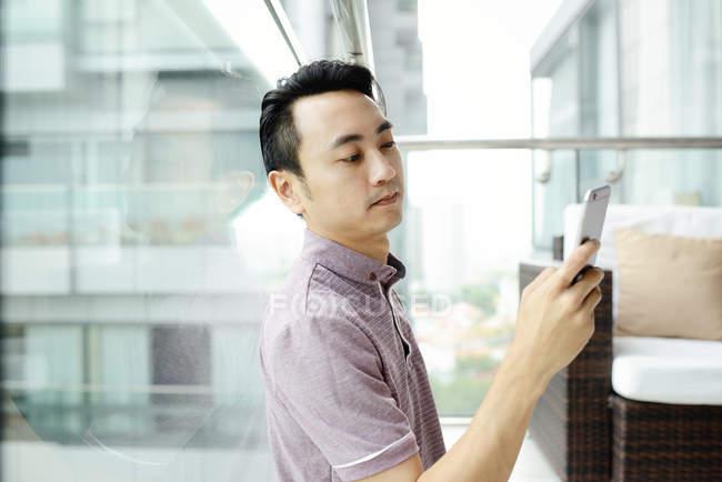 Зрілі азіатських випадковий людина за допомогою смартфона в домашніх умовах — стокове фото