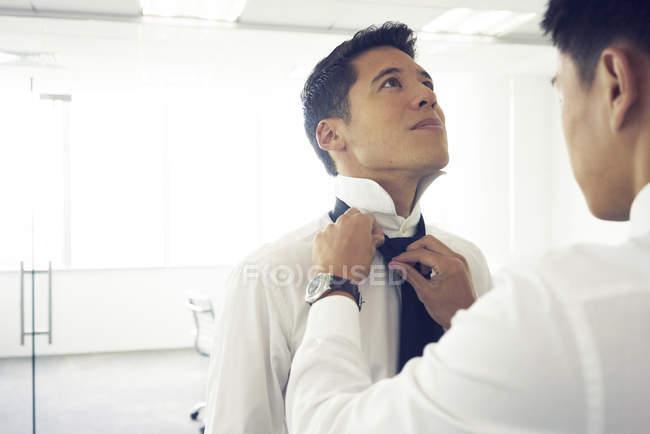 Mann mit Krawatte mit schönen asiatischen Geschäftsmann helfen — Stockfoto