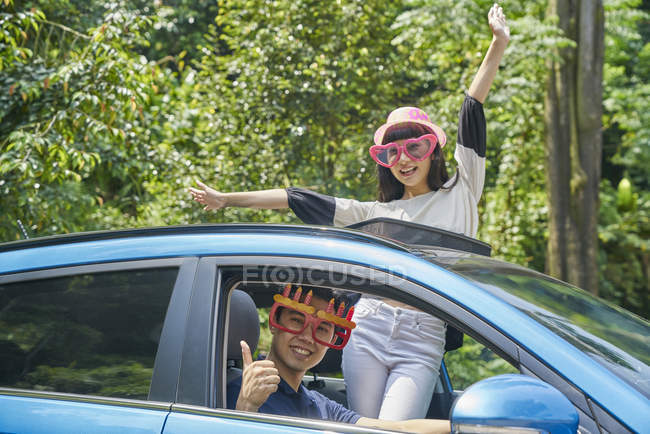 Couple standing through the sun roof of a car — Stock Photo