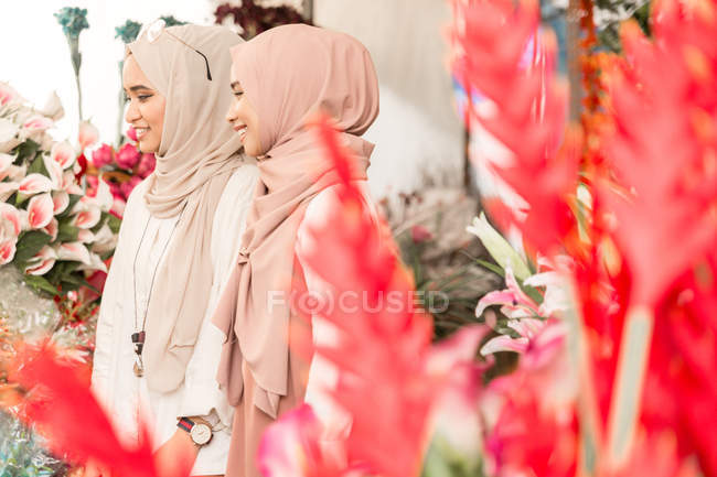 Two young muslim girls in flower shop having a fun conversation — Stock Photo