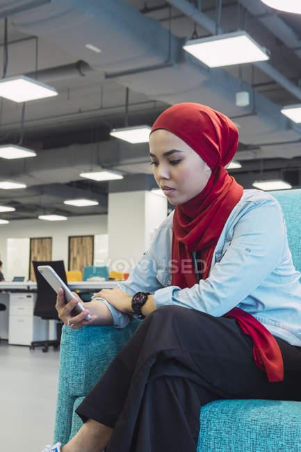 Jeune asiatique fortunée à l'aide de smartphone dans le bureau moderne — Photo de stock