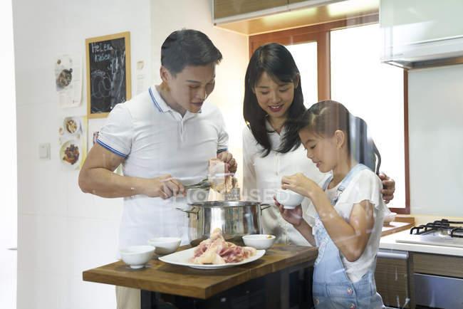 Feliz familia asiática, preparar la comida juntos en el hogar - foto de stock