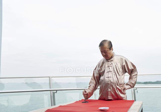 Vieil homme asiatique, dessin de hiéroglyphes de calligraphie au nouvel an chinois — Photo de stock