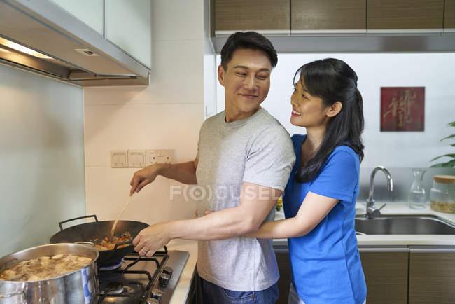 Happy asian couple preparing food at kitchen — Stock Photo