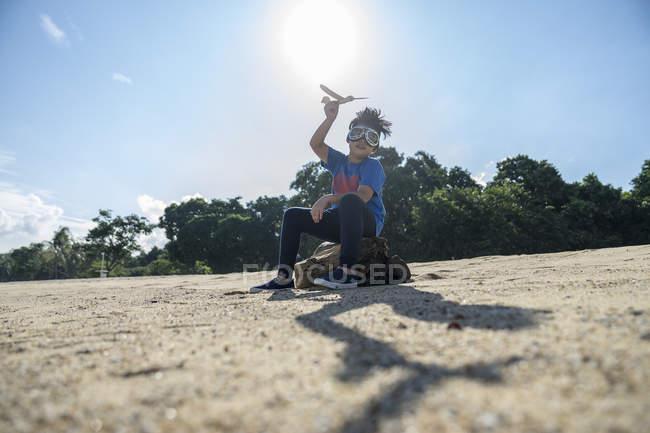 Bambino supereroe che gioca con un aeroplano giocattolo — Foto stock