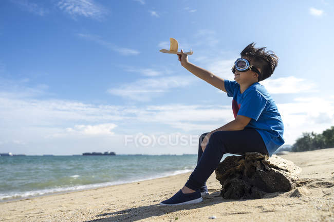 Superhero kid playing with a toy airplane — Stock Photo